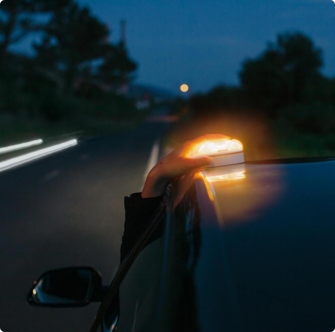 Persona colocando una baliza Help Flash en el techo del coche